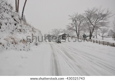 Road During Snowfall with car driving, blizzard on the road and bad visibility - stock photo