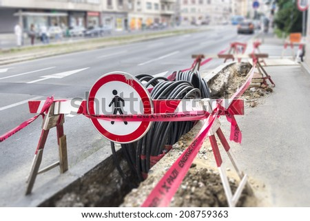 Road excavation at a construction site at conduits for the laying of fibre optic and electric cable  - stock photo