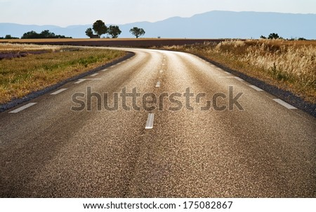 Road filling by sunlight through fields of Provence. - stock photo
