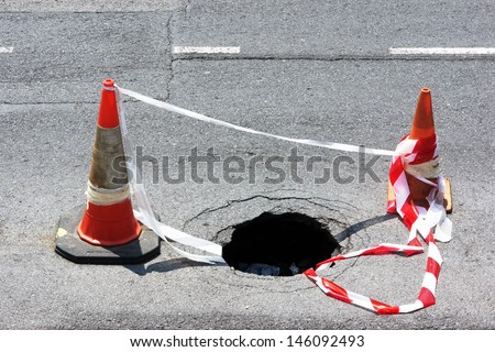 road hole with warning cones and tape - stock photo
