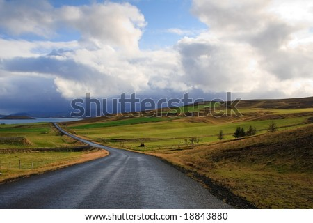 Road in bright green fields and hills in Iceland - stock photo