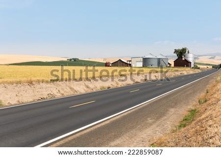 Road in eastern WA near Walla Walla approaching farm and barn with silo - stock photo