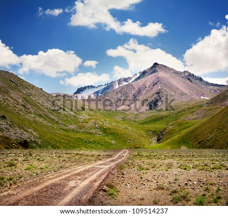 Road in mountains at blue sky in Kazakhstan, central Asia - stock photo