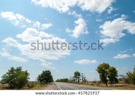 Road in nature on a sunny cloudy day - stock photo