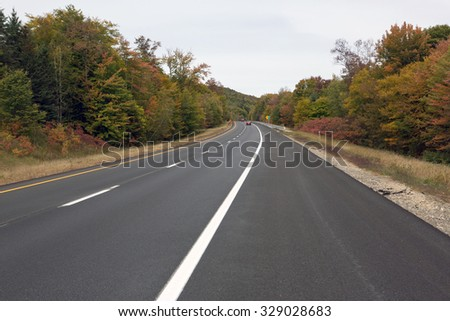 Road in New Hampshire and the forest at fall time - stock photo