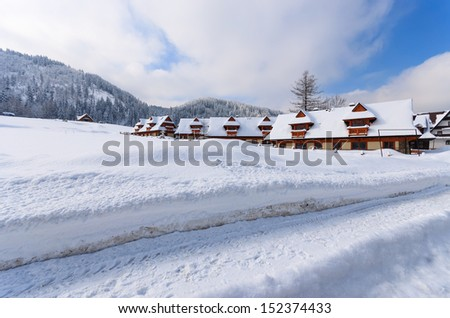 Road in snow and mountain cottage holiday houses in winter landscape of Tatry Mountains, Koscieliska valley, Zakopane, Poland - stock photo