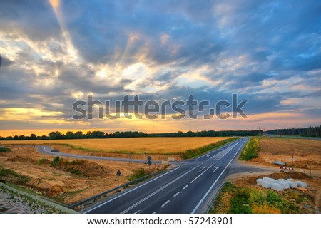 road in the fields of corn at the sunset - stock photo