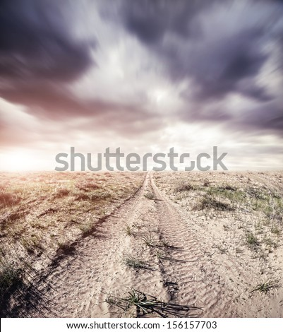 Road in the sands at dramatic overcast sky - stock photo