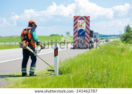 Road landscapers cutting grass around mileposts along the road using string lawn trimmers - stock photo