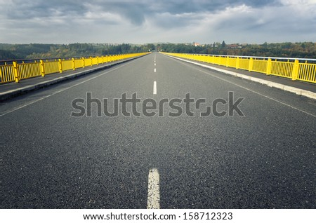 road leading to the bridge across the lake - stock photo