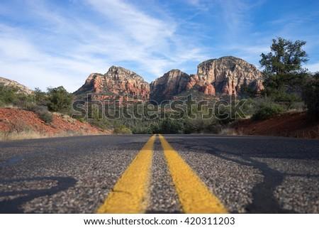road leading towards mountains in sedona arizona - stock photo