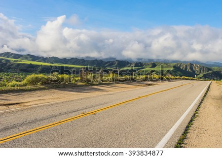 Road leads through the green hills of southern California near Santa Clarita. - stock photo