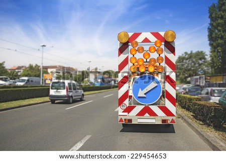 Road maintenance car signals detour due to roadworks - stock photo