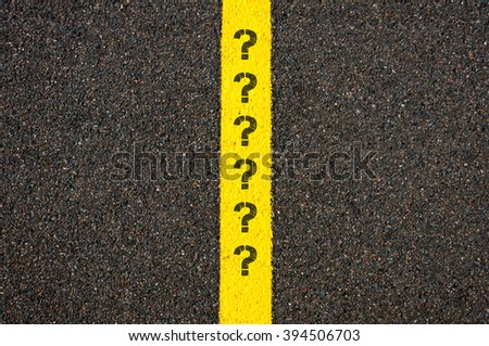 Road marking yellow paint dividing line with question marks, concept image - stock photo