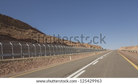 Road number 12, and a security fence on the border of Israel and Egypt - stock photo