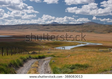 Road on a mountain plateau with the orange grass at the background of the valley of white river under a blue sky with white clouds, Plateau Ukok, Altai mountains, Siberia, Russia - stock photo