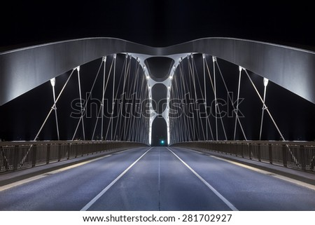 Road on modern frame bridge illuminated at night - stock photo
