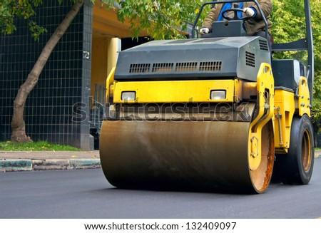 Road repair, compactor lays asphalt. - stock photo