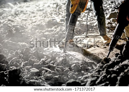 Road repairing works with jackhammer at night  - stock photo