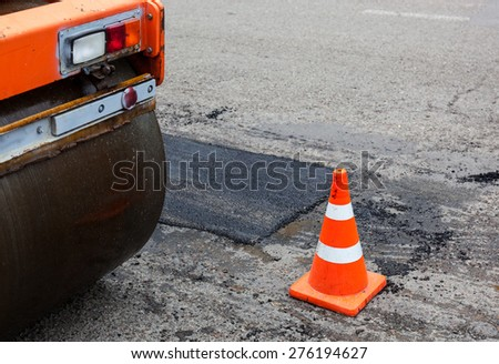Road roller and traffic cone on the road construction. - stock photo