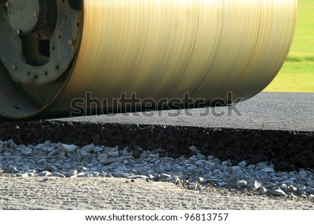 Road roller repairing asphalt pavement - stock photo