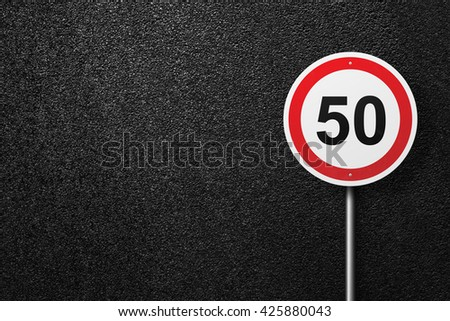 Road sign circular shape. The speed limit. Behind the signs one can see a smooth asphalt road. The texture of the tarmac, top view. - stock photo