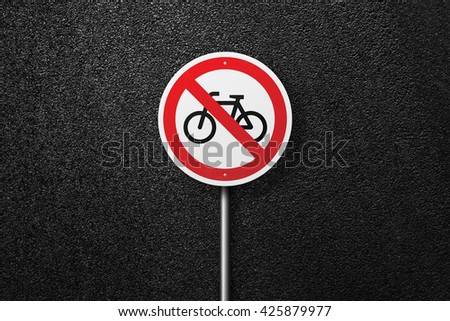 Road sign circular shape with a picture of the bike. Behind the signs one can see a smooth asphalt road. The texture of the tarmac, top view. - stock photo