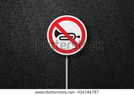Road sign circular shape with a picture of the musical instrument. Behind the signs one can see a smooth asphalt road. The texture of the tarmac, top view. - stock photo