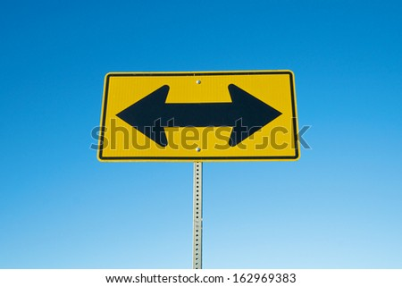 Road sign in yellow and black points the way to two opposite directions. - stock photo