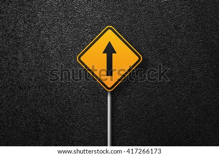 Road sign of the diamond shape with pointer. Behind the sign one can see a smooth asphalt road. The texture of the tarmac, top view. - stock photo