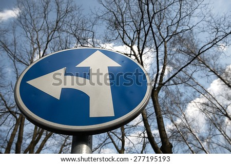 Road sign road fork standing on the street against the sky. - stock photo