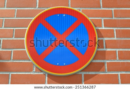 """Road sign """"The stop is forbidden"""" is fixed on a red brick wall - stock photo"""