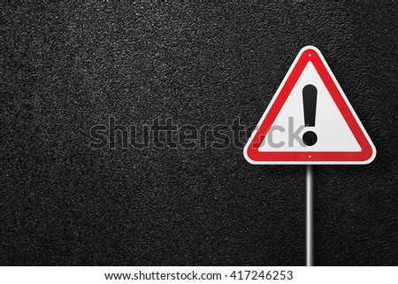 Road sign triangular shape with exclamation mark. Behind the signs one can see a smooth asphalt road. The texture of the tarmac, top view. - stock photo