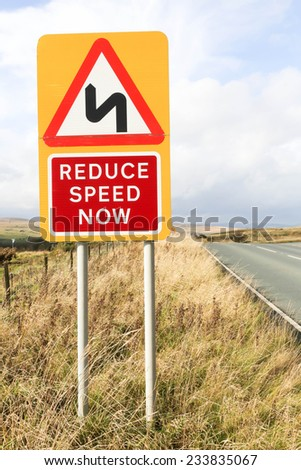 Road sign warning of a sharp bend ahead and to reduce speed on a yellow background against a partly cloudy sky. - stock photo