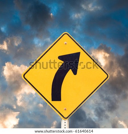 Road sign warning of dangerous curve with dramatic sky background. - stock photo