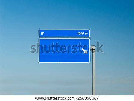 Road Sign with copyspace over blue sky in background - stock photo