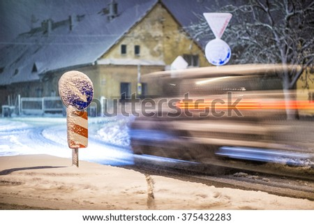 road sign with moving car on the street after snowstorm, winter and night photography, snow calamity - stock photo