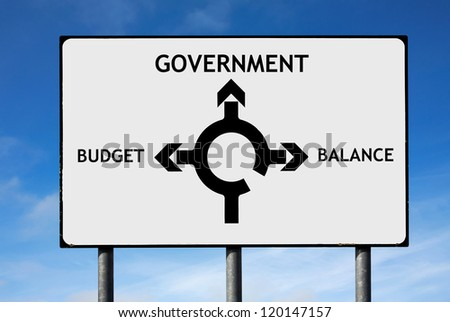 Road sign with roundabout directions pointing towards government budget and balance - stock photo