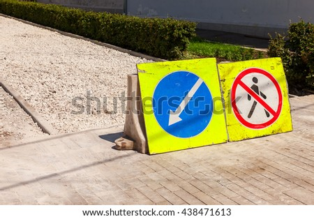 Road signs at the under construction sidewalk in summer day - stock photo