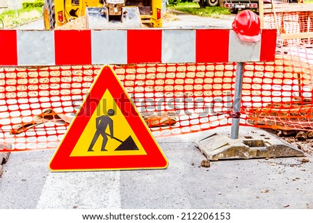 Road signs in a street, under reconstruction symbol - stock photo
