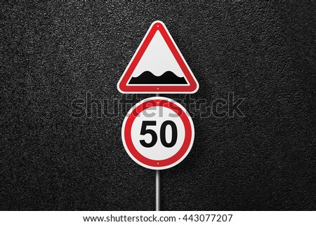 Road signs of the circular and triangular shape. Behind the signs one can see a smooth asphalt road. Rough roads. Speed limit. The texture of the tarmac, top view. - stock photo