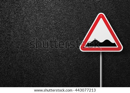 Road signs of the triangular shape. Behind the signs one can see a smooth asphalt road. Rough roads. The texture of the tarmac, top view. - stock photo