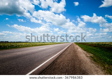 Road Through Field Russian Landscape. Car Travel Scenic Blue Sky Long Route. Adventures Concept - stock photo