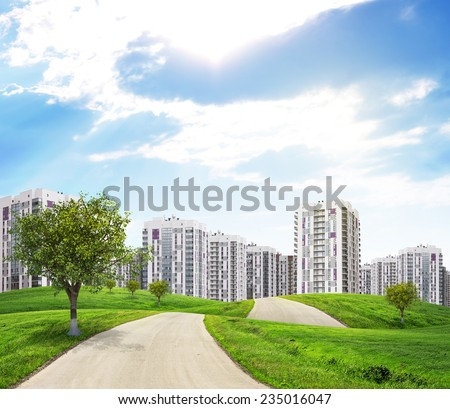 Road through green hills with a few trees, leading to city. Green tree on the fore. High-rise buildings as backdrop - stock photo