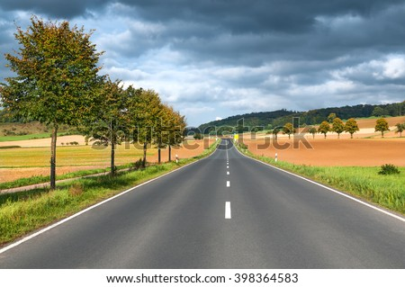 Road through landscape with harvested fields in early autumn with sunshine and approaching rain clouds; Rural traffic infrastructure - stock photo