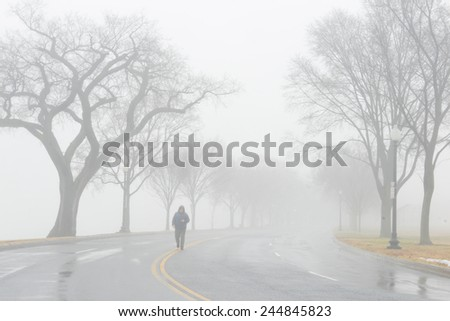 Road to fog and a man walks in to middle of road - stock photo