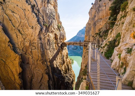 Road to the old beautiful and a very narrow bridge between two steep mountains over the canyon with mountain river at the bottom. Very windy and dangerous.  - stock photo