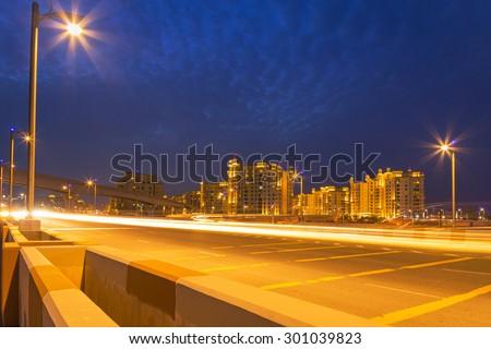 Road to the Palm Jumeirah island in Dubai at night, UAE - stock photo