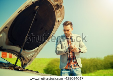 Road trip car trouble.A young man with a silver car that broke down on the road. - stock photo
