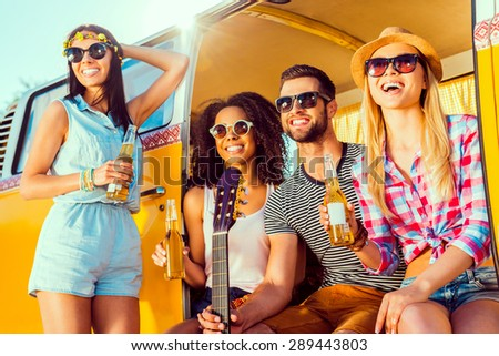 Road trip fun. Group of young happy people enjoying time together while sitting at their retro minivan  - stock photo